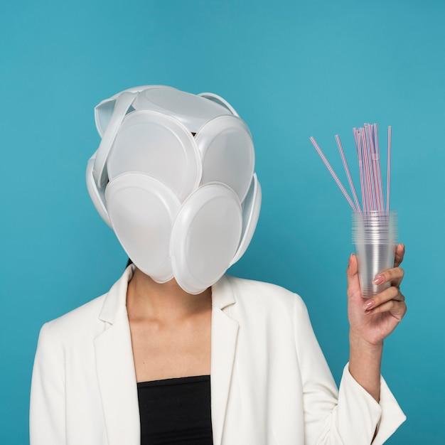 Gezicht van de vrouw bedekt met plastic borden en met plastic bekers en rietjes