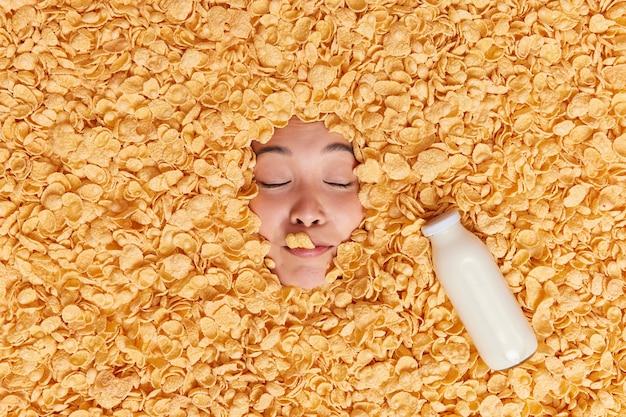Gezicht van de vrouw dat door cornflakes steekt heeft gezonde voeding houdt de ogen gesloten en drinkt verse melk