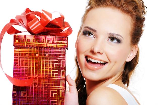 Gezicht van een gelukkig lachende vrouw met rode doos en opzoeken over witte ruimte