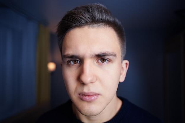 Gezicht van een jonge blanke man met bruine ogen, kort haar en een norse blik, tegen de muur van een donkerblauwe kamer.