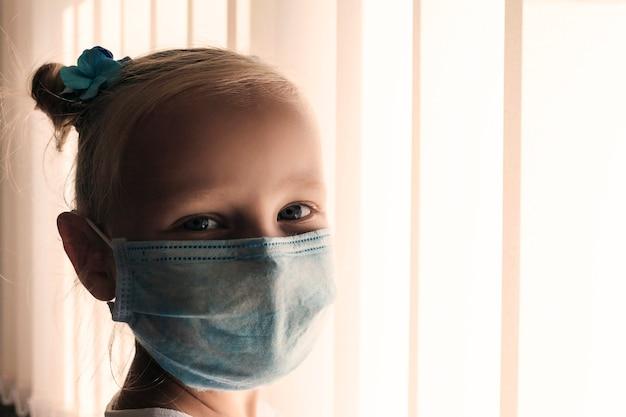 Gezicht van een klein meisje met een medisch masker op een lichte achtergrond kinderen in quarantaine met masker