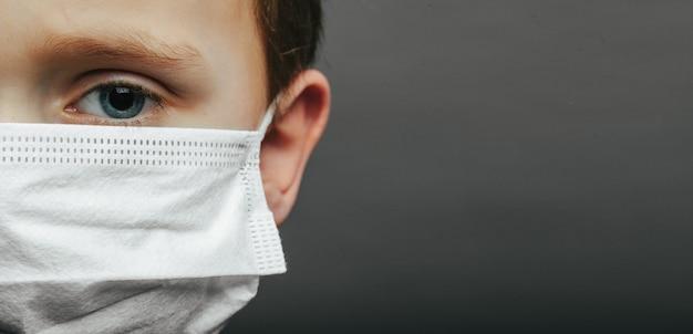 Gezicht van een masker-dragende jongen met angst in de ogen close-up op een grijze achtergrond.