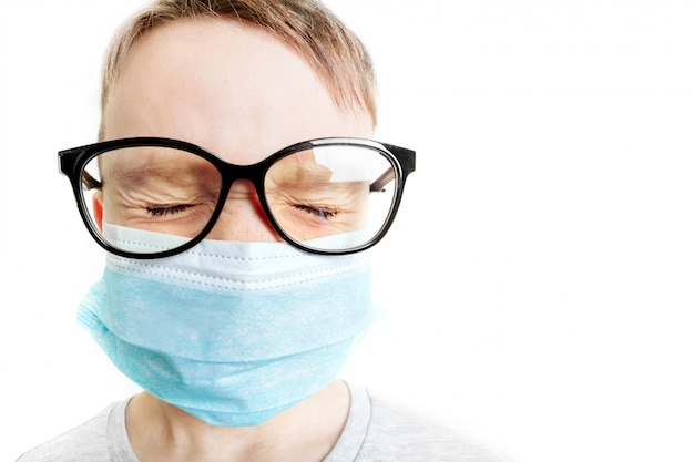 Gezicht van een masker-dragende jongen met angst in het oog close-up