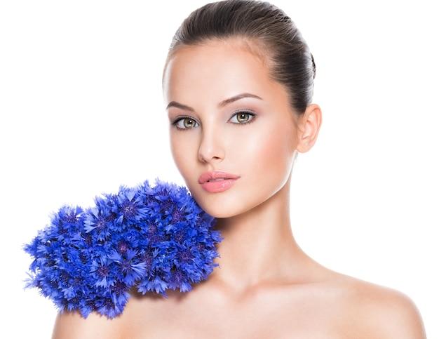 Gezicht van een mooi meisje met blauwe ruikertje bloemen