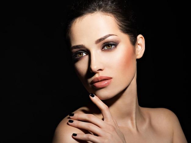 Gezicht van een mooi meisje met mode make-up en zwarte nagels poseren over donkere muur