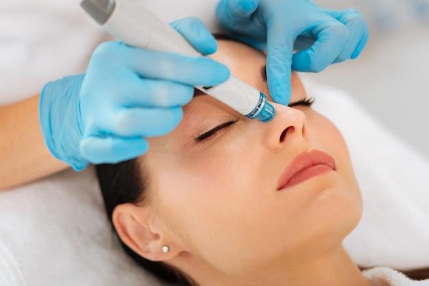 Gezicht van een mooie goo ogende vrouw tijdens hydrafacial procedure in de schoonheidssalon
