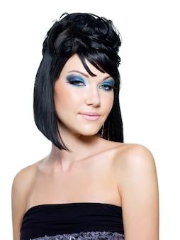 Gezicht van een mooie jonge vrouw met helderblauwe make-up. geïsoleerd op wit