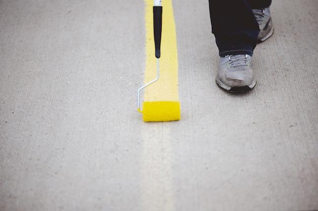 Gezicht van een persoon die de parkeerlijnen van het asfalt van een parkeerplaats opnieuw schildert met gele verf