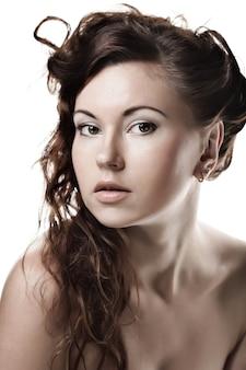 Gezicht van een sexy mooie jonge vrouw met schone huid op een witte muur