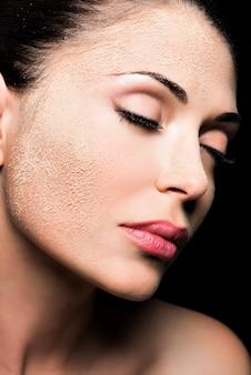 Gezicht van een vrouw met cosmetisch poeder op de huid