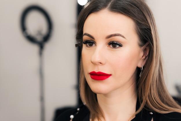 Gezicht van een vrouw met professionele lichte make-up met rode lippenstift in een schoonheidssalon