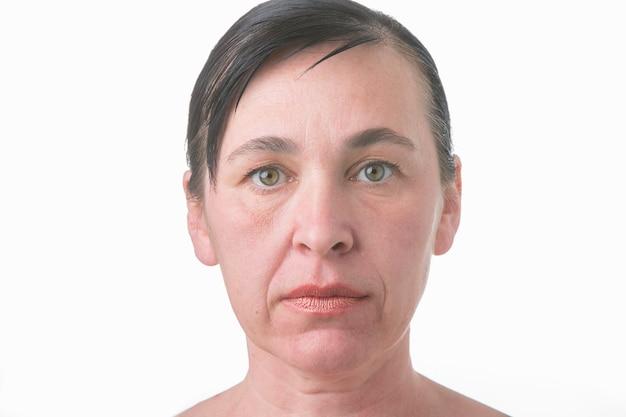 Gezicht van een vrouw met rimpels. portret van een oudere vrouw zonder behandeling op een wit