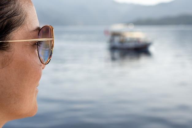 Gezicht van een vrouw van middelbare leeftijd kijkt naar de zee zittend op het strand, reizend gelukkig rustend vrouwelijk uiterlijk