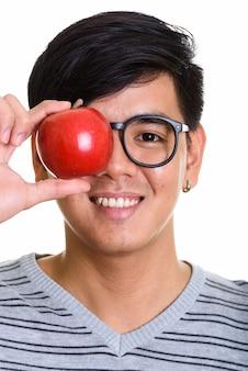 Gezicht van gelukkige aziatische man die lacht terwijl hij oog bedekt met rode appl