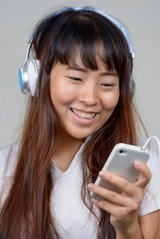 Gezicht van gelukkige jonge aziatische vrouw met behulp van telefoon tijdens het luisteren naar muziek