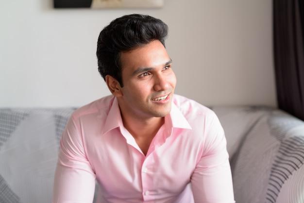 Gezicht van gelukkige jonge indiase zakenman denken en kijkt uit het raam thuis