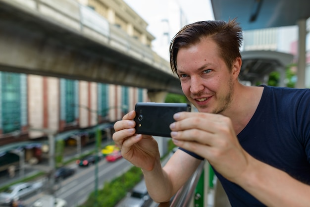 Gezicht van gelukkige jonge knappe man die foto met telefoon op sky train station