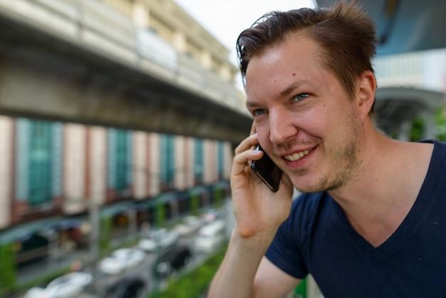 Gezicht van gelukkige jonge knappe man praten aan de telefoon op sky train station