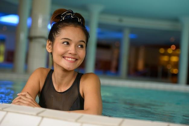Gezicht van gelukkige jonge mooie aziatische toeristenvrouw die en bij de kuuroord denken ontspannen