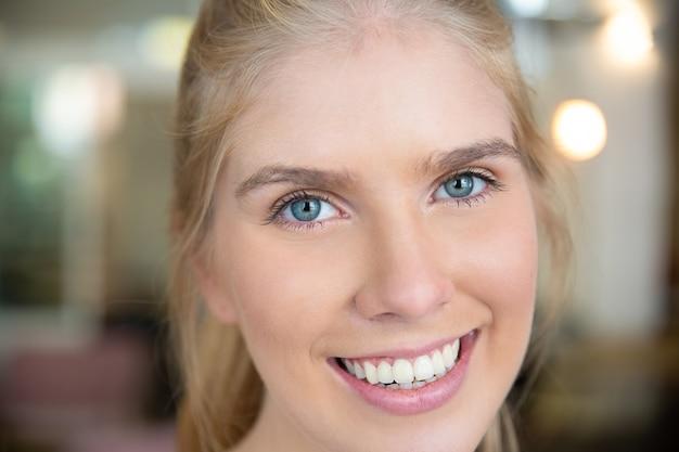 Gezicht van gelukkige mooie jonge blonde vrouw met blauwe ogen en witte tanden