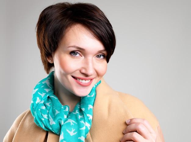 Gezicht van gelukkige vrouw in beige herfstjas met groene sjaal op grijze achtergrond
