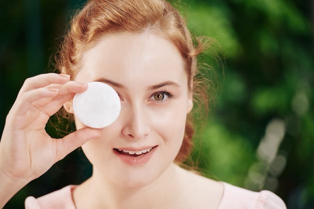 Gezicht van glimlachende jonge vrouw die oog behandelen met wattenschijfje en camera bekijken