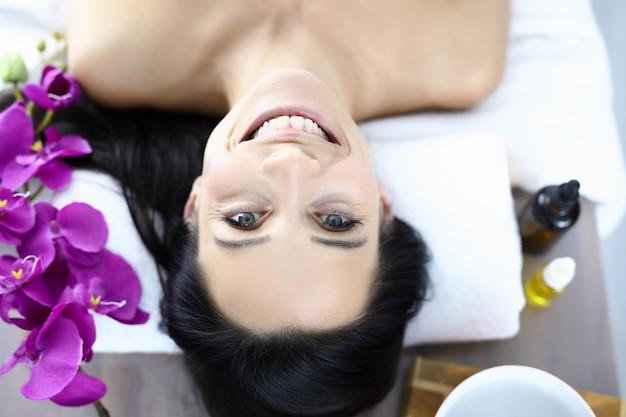 Gezicht van glimlachende vrouw in kuuroord. gezichtsverzorging en verjonging concept