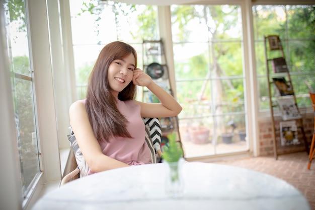 Gezicht van het mooie aziatische jongere vrouw glimlachen met geluk in woonkamer