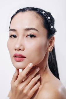 Gezicht van jonge aantrekkelijke aziatische vrouw met perfecte skintouching kin en voorzijde kijken