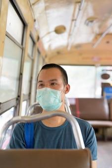 Gezicht van jonge aziatische man met masker rijden de bus met afstand