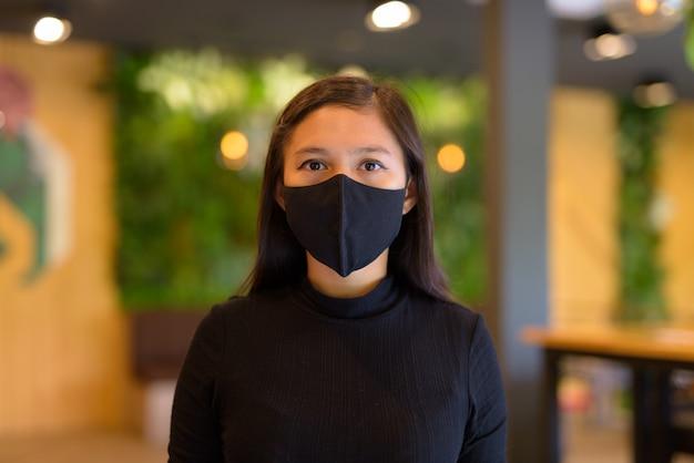 Gezicht van jonge aziatische onderneemster die masker en sociaal afstand nemen bij de koffiewinkel draagt