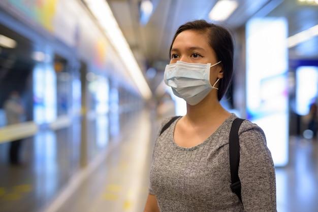 Gezicht van jonge aziatische vrouw met masker voor bescherming tegen uitbraak van coronavirus te wachten op het metrostation