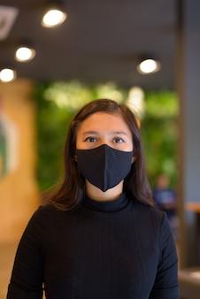Gezicht van jonge aziatische zakenvrouw die masker draagt voor bescherming tegen de uitbraak van het coronavirus in de coffeeshop