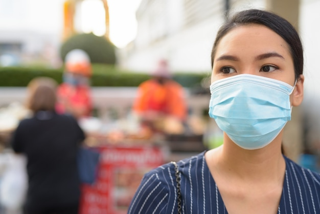 Gezicht van jonge aziatische zakenvrouw met masker voor bescherming tegen uitbraak van het coronavirus, denken in de stad