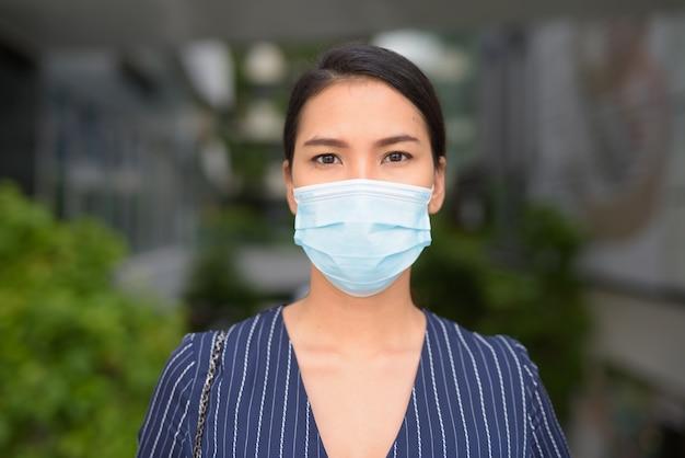 Gezicht van jonge aziatische zakenvrouw met masker voor bescherming tegen uitbraak van het coronavirus in de stad