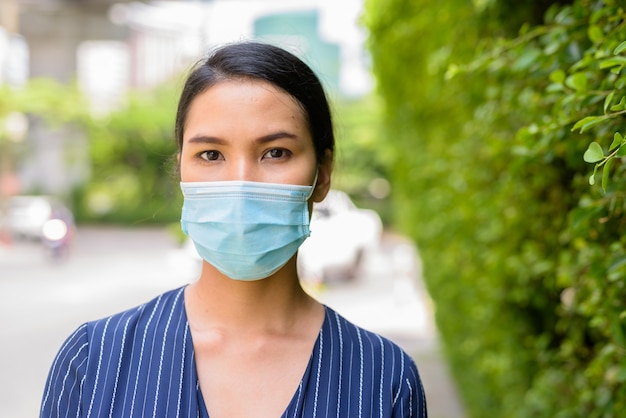 Gezicht van jonge aziatische zakenvrouw met masker voor bescherming tegen uitbraak van het coronavirus in de straten buitenshuis