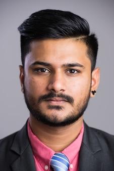 Gezicht van jonge ernstige knappe indiase zakenman