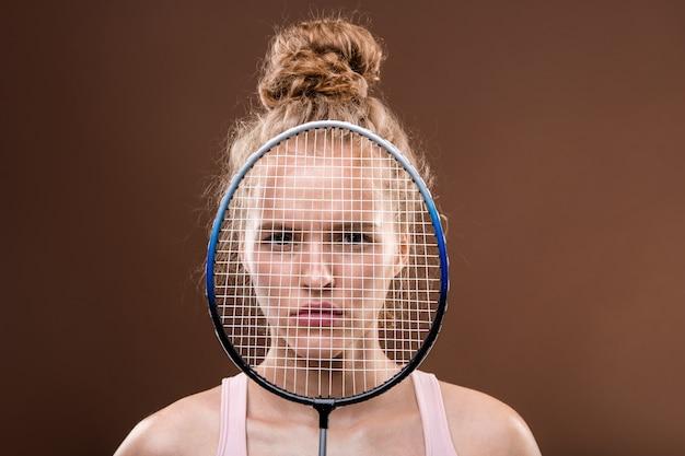 Gezicht van jonge ernstige sportvrouw met blond haar op zoek naar jou van achter tennisracket