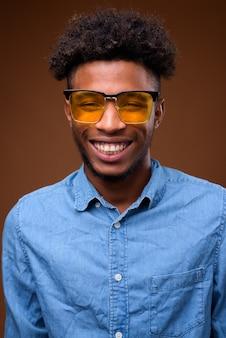 Gezicht van jonge gelukkig afrikaanse man die lacht op bruin