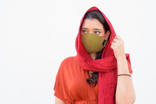 Gezicht van jonge indiase vrouw met hoofddoek en masker denken tegen een witte achtergrond