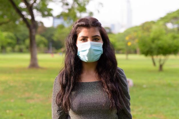 Gezicht van jonge indiase vrouw met masker ontspannen in het park