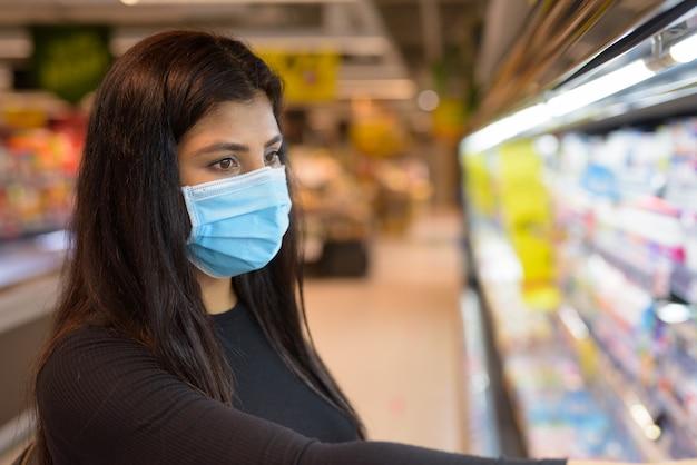 Gezicht van jonge indiase vrouw met masker winkelen met afstand bij de supermarkt