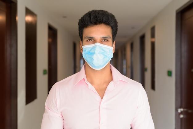Gezicht van jonge indiase zakenman die masker draagt voor bescherming tegen uitbraak van het coronavirus in de gang