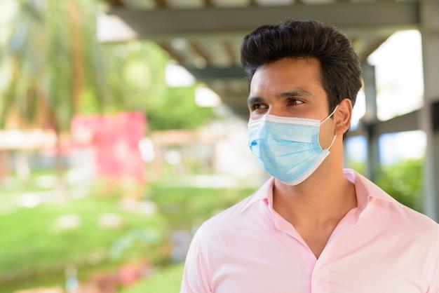 Gezicht van jonge indiase zakenman masker dragen en denken in het park