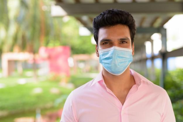 Gezicht van jonge indiase zakenman masker dragen in het park