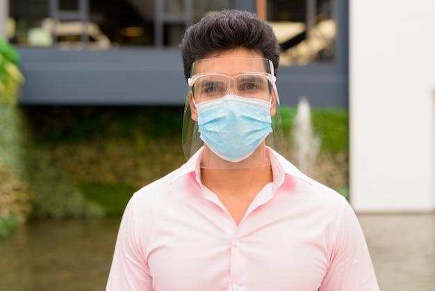 Gezicht van jonge indiase zakenman met masker en gezichtsschild in de stad buiten