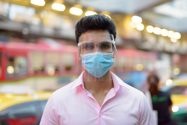 Gezicht van jonge indiase zakenman met masker en gezichtsschild in de stadsstraten buitenshuis