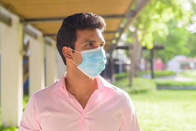 Gezicht van jonge indiase zakenman met masker voor bescherming tegen uitbraak van het coronavirus, denken in het park