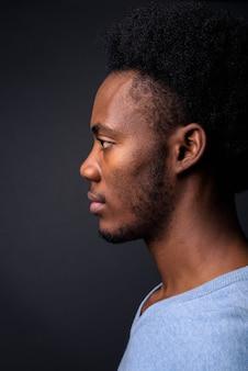 Gezicht van jonge knappe afrikaanse man tegen een grijze achtergrond