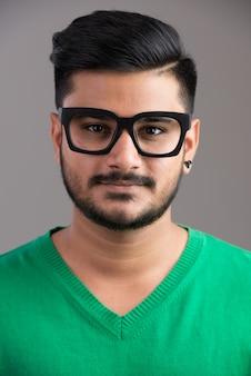 Gezicht van jonge knappe indiase man met bril